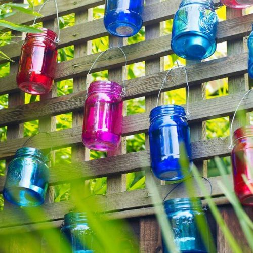 Garden fence ideas with latticework top and hurricane lights