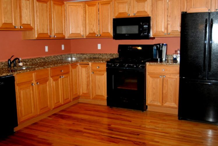 Kitchens with black appliances and Honey oak cabinets