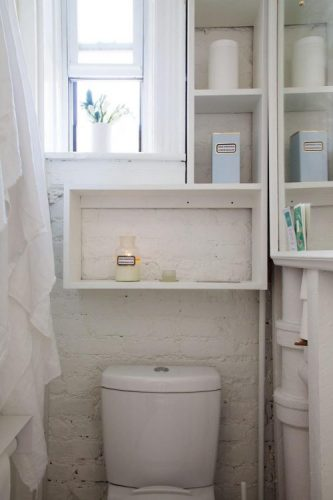 Tiny intense and airy bathroom with a paintinged brick wall