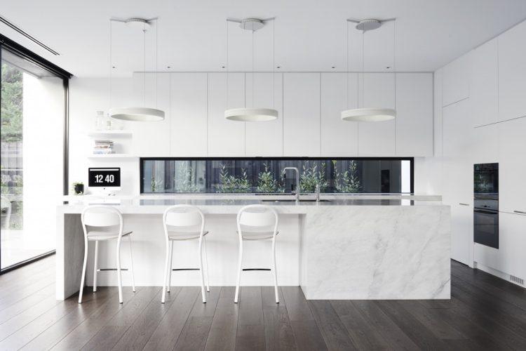 White marble island kitchen with dark wood floors